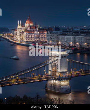 Budapest, Hungary - Beautiful illuminated Szechenyi Chain Bridge with the Parliament of Hungary at blue hour with sightseeing boat on River Danube - Stock Image