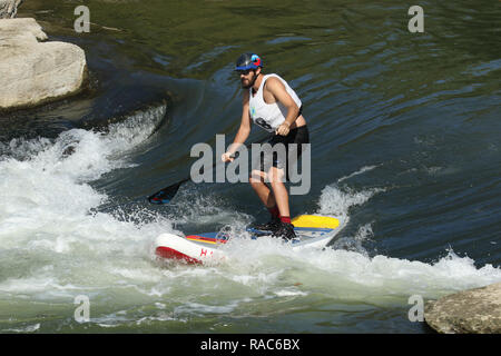 Standup Paddleboarder rides through a water trough. At the Whitewater feature in the Mad River. Wagner Subaru Outdoor Experience at Eastwood Metro Par - Stock Image