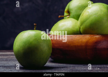 Green apple close up on a table on a dark background - Stock Image