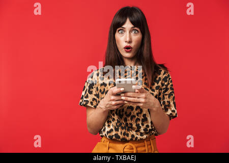 Photo of excited surprised woman 30s dressed in stylish outfit wondering while holding smartphone isolated over red background - Stock Image