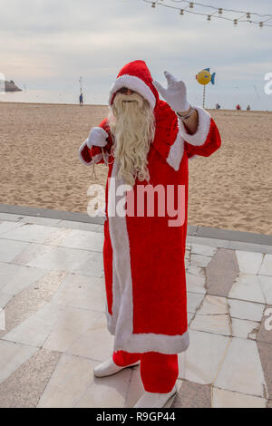 Benidorm, Costa Blanca, Spain, 25th December 2018. British tourists dress for the occasion on Christmas Day in this favourite getaway destination for Brits escaping the cold weather at home. Temperatures will be in the mid to high 20's Celsius today in this mediterranean hotspot. Man on Levante beach promenade wearing full santa outfit with beard and sack. - Stock Image