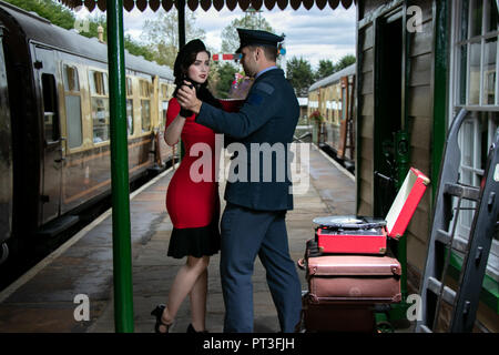 Attractive couple, handsome man in uniform, beautiful woman in dress, dancing on railway platform with portable record player - Stock Image