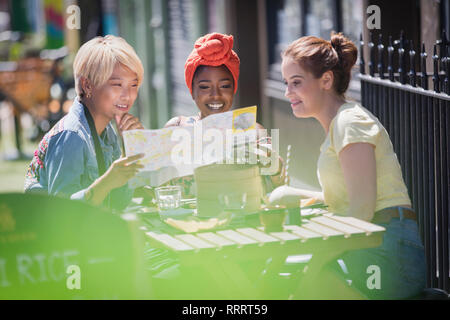 Young women friends looking at map, enjoying lunch at sunny sidewalk cafe - Stock Image