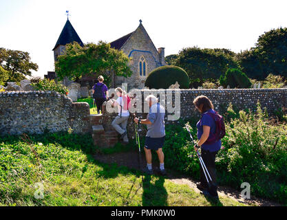Walkers on public foot path at Snow Hill crossing  the stile in the flint wall over to st peter and paul church West Wittering, West Sussex, UK - Stock Image
