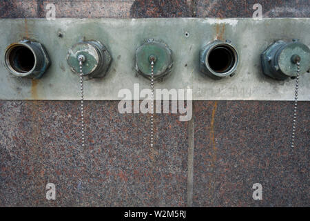 Five standpipe connections aligned on the side of a building, three closed, two open - Stock Image