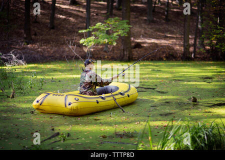 Man fishing while sitting in inflatable raft on swamp - Stock Image