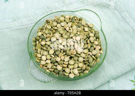 Split Green Peas in vintage glass dish on old linen napkins - Stock Image