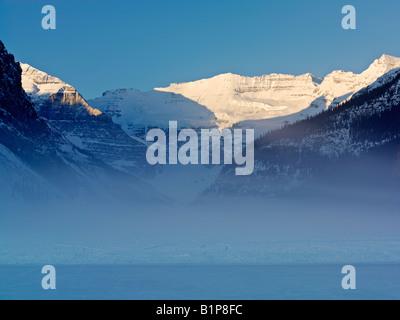 Canada Alberta Banff National Park Lake Louise sunrise on Mount Victoria on Lake Louise with mist rising on frozen - Stock Image
