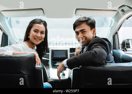 two asian people in suit driving a car looking back to camera - Stock Image