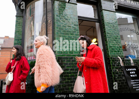 Trendy fashionable young women shoppers outside the Labour and Wait shop in winter in Redchurch Street Shoreditch East London  E2 UK   KATHY DEWITT - Stock Image