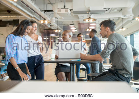 Colleagues at table with laptop - Stock Image