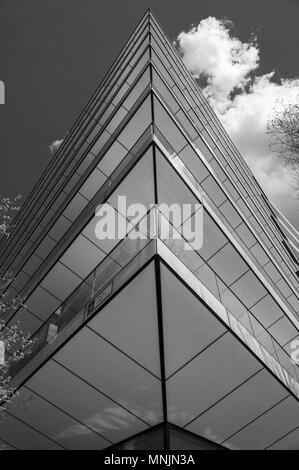 Black and white image of the sharp, angular corner of a modern city building - Stock Image