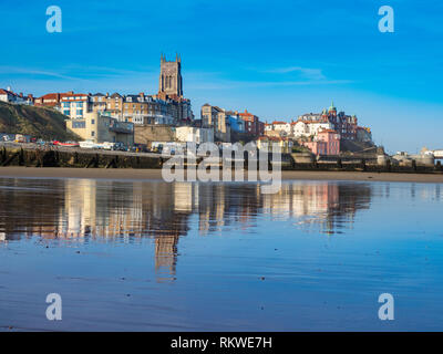 View of Cromer town with reflection on the wet sand. - Stock Image