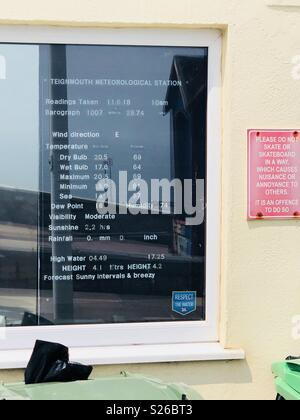 Teignmouth meteorological station sign displaying the temperature, visibility, wind direction and height of water - Stock Image