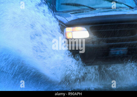 Closeup of the front end of a car going through a mud puddle. - Stock Image