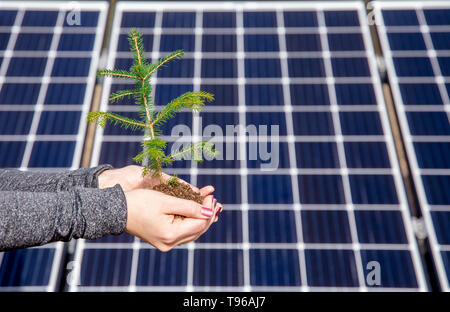 Saving nature by using green solar energy concept. And accidentally also funny optical illusion concept, dots flickering, changing places on the backg - Stock Image