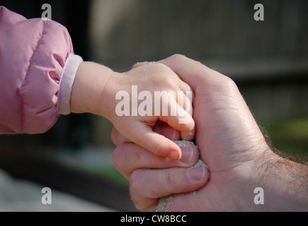 Father & Child Gripping Hands - Stock Image