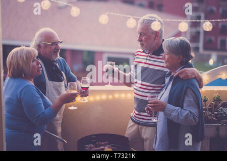 Night friends people celenbrate together with red and white wine having fun together - city view on terrace - barbecue and friendship for adult senior - Stock Image