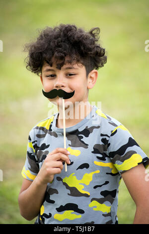Playful young boy holding up a mustache party accessory with smiling eyes outdoors against blurred green grass - Stock Image