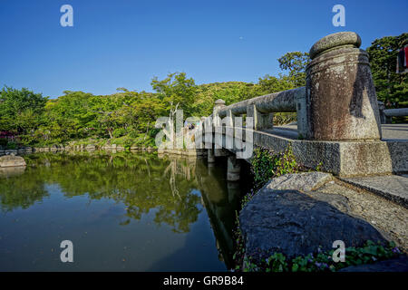 Low Angle View Of Bridge Over Lake Against Trees And Sky - Stock Image