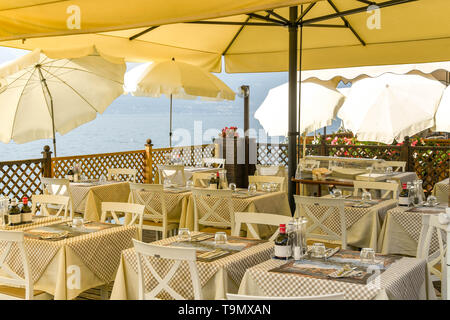 TORRI DEL BENACO, LAKE GARDA, ITALY - SEPTEMBER 2018: Outdoor dining area with tables laid out under a canopy at a restaurant on Lake Garda - Stock Image
