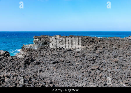Edge of volcanic lava field looking over the Atlantic Ocean at Playa de Puerto Naos, La Palma, Spain - Stock Image