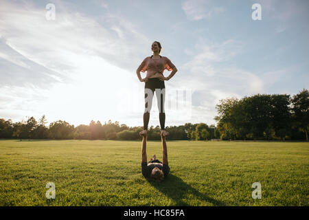 Outdoors shot of young couple doing acrobatic yoga exercise in park. Woman standing on feet of man and balancing. - Stock Image