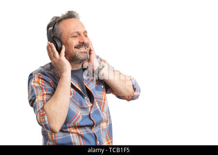 Cheerful man with headphones listening and enjoying music as break time concept isolated on white background - Stock Image