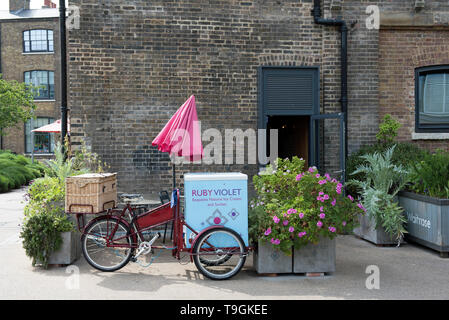 Ruby Violet Ice Cream bicycle tricycle with red sunshade next to planters in front of shop Kings Cross London England Britain UK - Stock Image