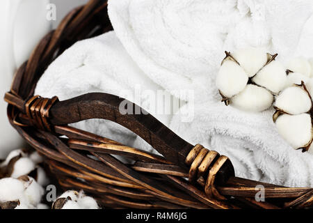 Laundry basket filled white fluffy towels, cotton flowers and a bottle of liquid soap against a blurred grey background. - Stock Image