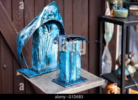 Wooden blue carved art figures in shop exterior in Kazimierz Dolny, Poland, Europe, bohemian tourist travel destination. - Stock Image