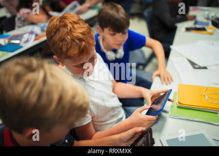 Junior high school boy students using digital tablets at desk in classroom - Stock Image