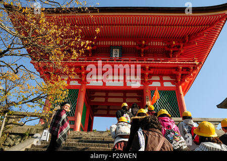 A female foreign tourist is overtaken by a tour party at the entrance to Fushimi Inari Shrine, Kyoto, Japan - Stock Image
