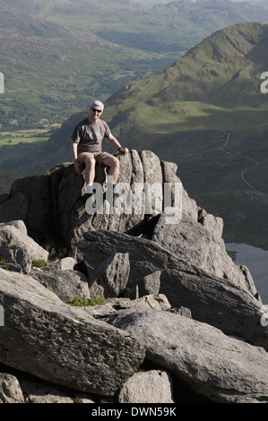 A hiker resting on a rock outcrop near Glyder Fach in the Snowdonia mountain range in Wales. - Stock Image