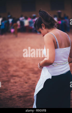 Mali, Africa - Young caucasian girl volunteer wearing a white t-shirt uniform while playing soccer with black african children, boys and adults in a r - Stock Image