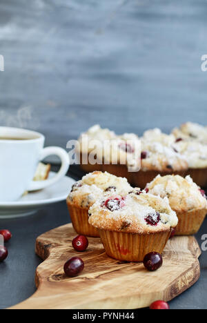 Cranberry Muffins on a wood cutting board with more cooling on a bakers rack. Extreme shallow depth of field with selective focus on muffin in foregro - Stock Image