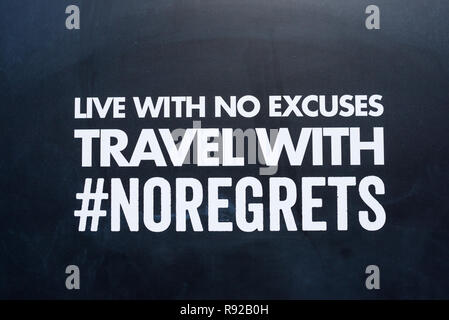 Live with no excuses travel with no regrets message written on capital white letters on a black background. #no regrets hashtag - Stock Image