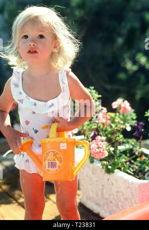 Blond Toddler Girl in a  swimsuit with a Toy Watering Can, USA - Stock Image