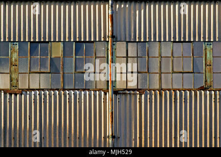 Rusting window frames and corrugated sheeting on a dilapidated building caught in late afternoon light. - Stock Image