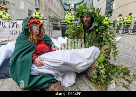 London, UK. 21st December 2018. Climate campaigners from Extinction Rebellion hold a wrapped mannequin represting a child burnt in a Greek wildfire at the protest at the BBC calling it to stop ignoring the climate emergency & mass extinctions taking place and promoting destructive high-carbon living through programmes such as Top Gear and those on fashion, travel, makeovers etc. The protest, organised by the Climate Media Coalition (CMC) and its director Donnachadh McCarthy brought mannequins wrapped in white cloth to the BBC representing the bodies of a Greek village killed by fire. Peter Mar - Stock Image