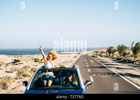 Happy cheerful couple of young caucasian crazy woman with curly hair enjoy the travel and vacation staying outside the roof of a convertible car with  - Stock Image