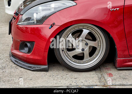 Suzuki VVT car lowered to sit barely above street level - Stock Image