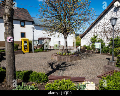 Central meeting place in village Niederstadtfeld, public bookshelf, sitting area, spring, near Daun, Eifel, Germany - Stock Image