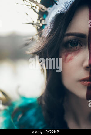 Half-face portrait of young woman in the image of a fairy and a sorceress in a dress and a crown. - Stock Image