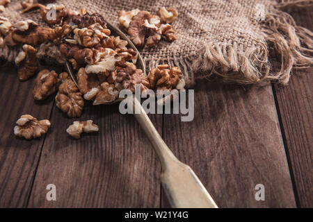 Walnuts on an old spoon and composition from old wood and material - Stock Image