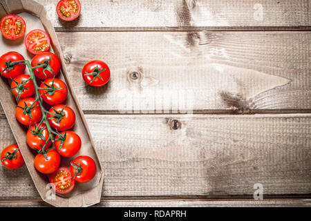 Fresh cherry tomatoes in the tray. On a wooden background. - Stock Image