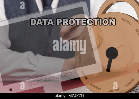 business man sitting behind desk pressing virtual screen with a locked padlock and computer screen and the words DATA PROTECTION. - Stock Image