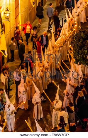 High angle view of hooded penitents (Nazarenos) in the procession of the Brotherhood (Hermandad) La Candelaria, Holy Week (Semana Santa), Seville, And - Stock Image