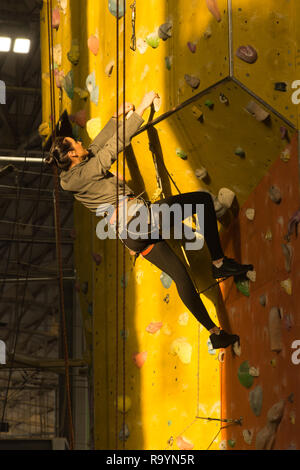 Young woman climbing a wall inside the Calshot Activities Centre, Hampshire, UK - Stock Image