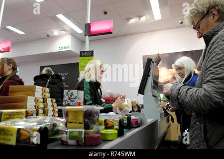 An older woman worker working at the checkout counter during Christmas  in M&S Marks and Spencer food grocery store in Great Britain UK. KATHY DEWITT - Stock Image